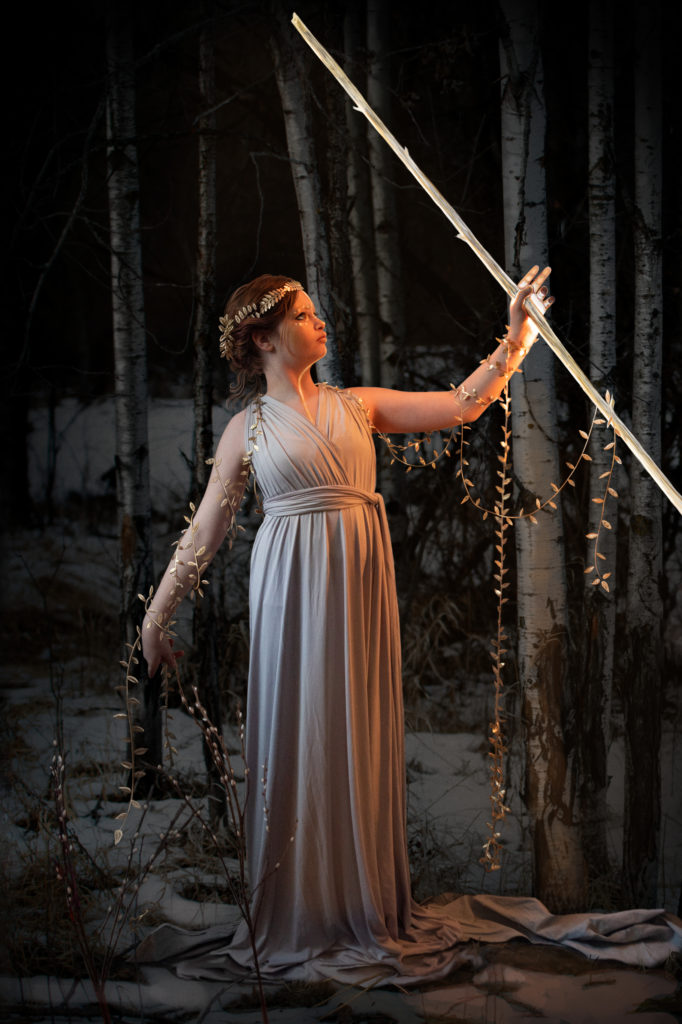 Young woman in simple draped dress, standing in a grove of trees, with gold leaves on vines around her arms. She has gold paint down her face and sternum, and holds a glowing staff in the air.